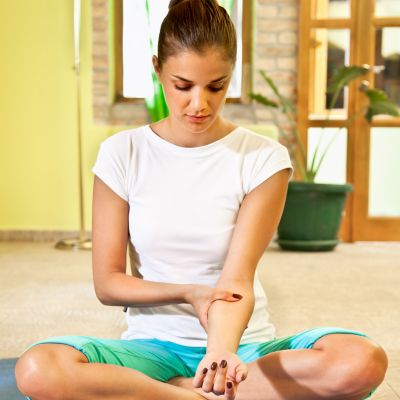 Happy young woman doing arm self massage at home. Healthy life.